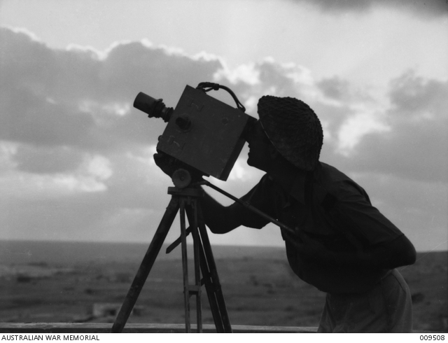 Tobruk, Libya. 1941-08. Damien Parer, a Department of Information photographer, filming with a Newman-Sinclair 35mm camera, probably the Auto Kine Camera model, during the Siege of Tobruk. Parer could be filming material for the Department of Information production, Siege of Tobruk. (See AWM Film F01097)