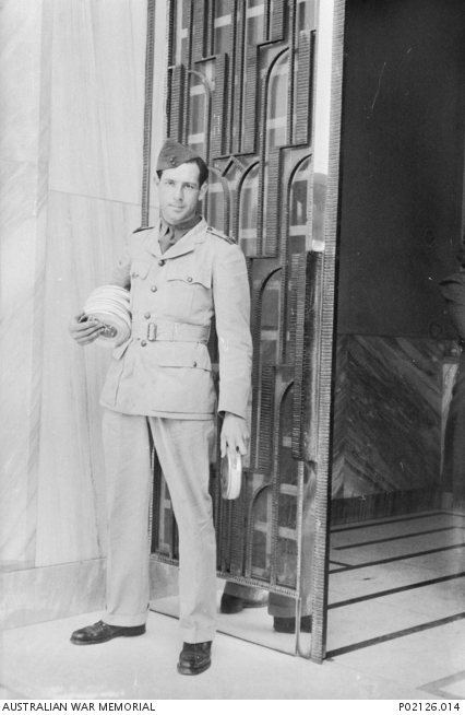 Middle East. c.1941-02. Portrait of Damien Parer standing holding cans of film. Parer was an official Australian war correspondent, photographer and film cameraman with the Department of Information. He served in the Middle East, Greece and the South-West Pacific from 1940 until his resignation in May 1943. He was killed on 17 September 1944 while filming front line operations with the US Marine Corps on Peleliu Island. (Original nitrate negative held in AWM Archive Store)